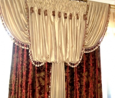 Торжественная портьера с напуском и свагами, щедро украшенная тесьмой с кистями.